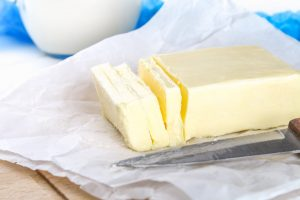 A bar of butter on a wooden board with a knife, on a white table. Ingredients for cooking